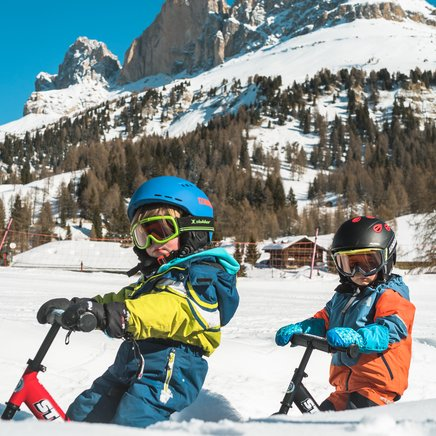 Kids with snowbike in the Kinderland Carezza with Catinaccio