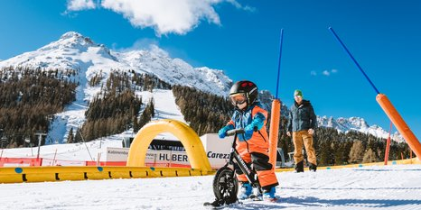 Kid with snowbike and dad in the Kinderland Carezza