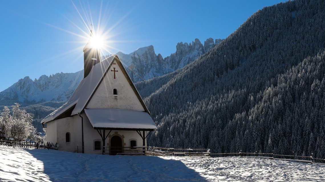 St. Sebastian chapel in Nova Levante under the snowy Latemar